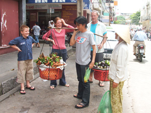 Ardi carrying shoulder sling of vegetable baskets in streets of Saigon