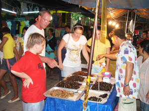 The Grangers at the bug booth at a night market in Phuket, Thailand