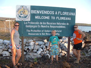 Emily, Amanda, and Gregg II in front of welcome sign to Floriana, Galapagos